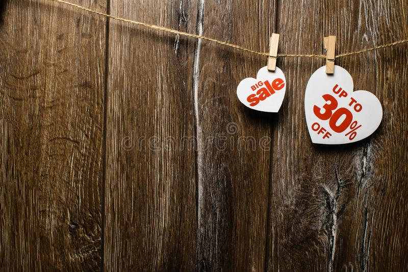 Hearts and discounts with romantic pattern on wooden background. Big sale on one heart. And thirty percent on another hanging on rope by clothespins royalty free stock photo