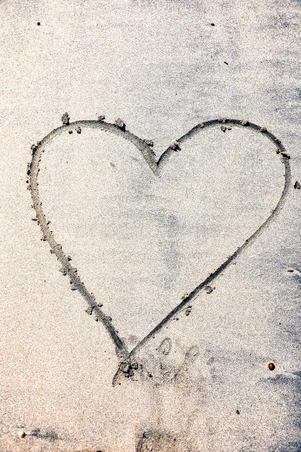 Hearts drawn on the sand of a beach. The inscription happy heart. Love sign stock photos