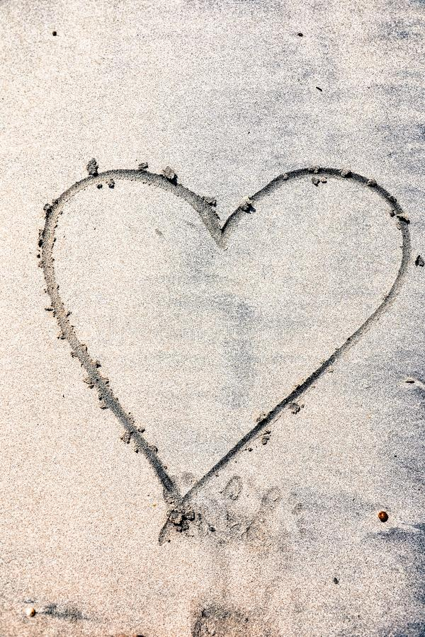 Hearts drawn on the sand of a beach. The inscription happy heart stock photo