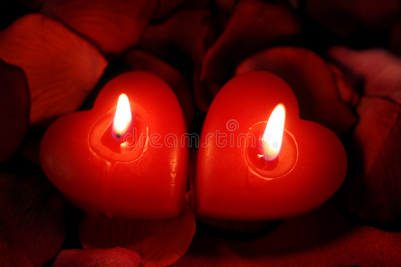 Hearts in harmony. Two heart-shaped candles, burning together in harmony royalty free stock photos