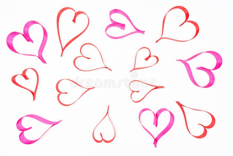 Hearts made from pink and red, satin ribbon on white background with clipping path, view from the top. Valentines Day concept. stock image