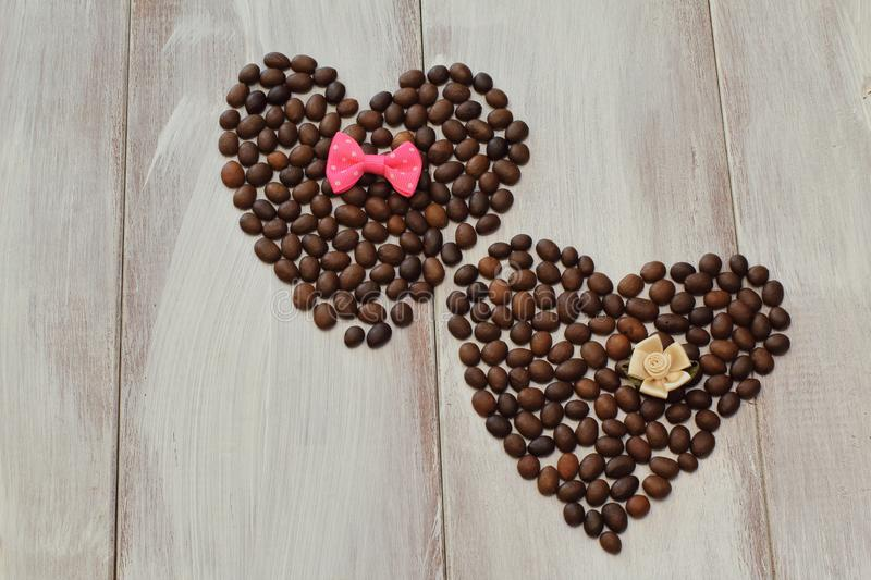 Hearts from roasted coffee beans decorated with red bow tie and delicate satin decorative flower of pastel color on light wooden stock images
