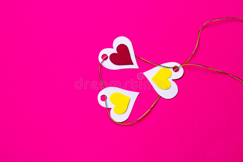 Hearts to hearts on a pink background and copy space. Hearts of paper - colorful. Pink background and copy space. Three hearts hanging on a rope. connected stock photo