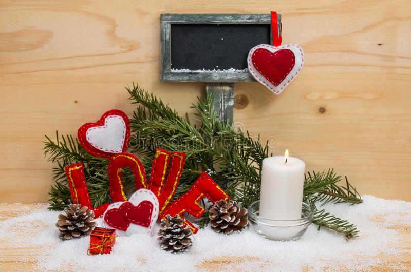 Hearts and the word love made of cloth with burning candle. Hearts and the word love made of cloth with burning candle and a sign for text on wooden background stock photo