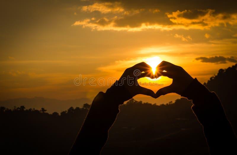 Heartsets de main de silhouettes et l'orange de ciel photo libre de droits