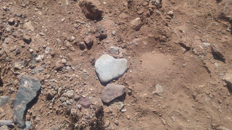 Heartshaped Felsen auf einer sandigen Straße lizenzfreies stockbild
