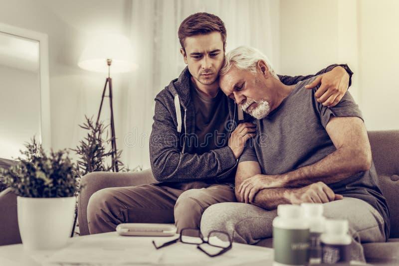 Heartsore wnuk ściska jego starszego srebrnowłosego dziadka i pociesza obraz stock