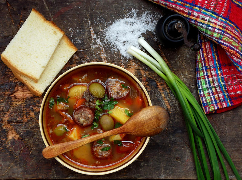 Hearty homemade soup with potatoes, carrots, sausages and olives in a clay bowl on a wooden background. royalty free stock images
