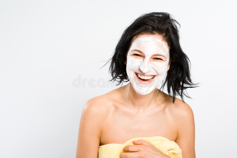 Hearty laughing. Really hearty laughing - nice woman with face mask wrapped into bath towel royalty free stock photography