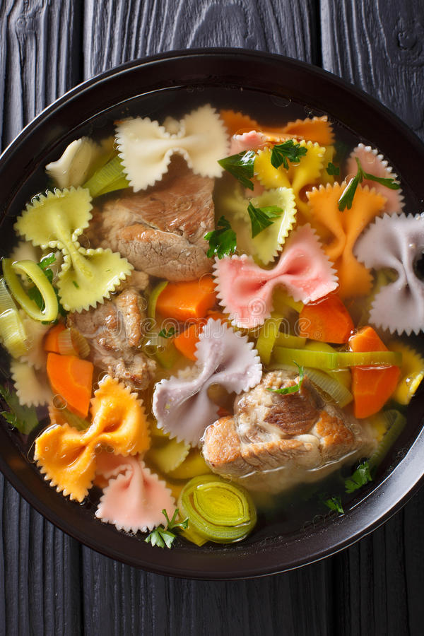 Hearty meat soup, with colored farfalle pasta and vegetables close-up. Vertical top view stock photography