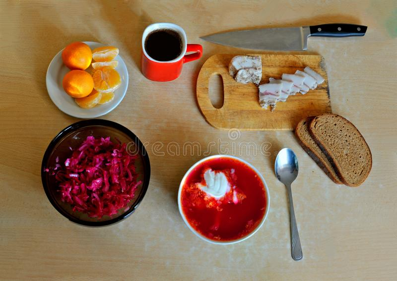 Hearty Russian lunch: borsch with sour cream, sauerkraut salad, rye bread, salted lard, three tangerines and black coffee. Hearty Russian lunch: borsch with stock photography