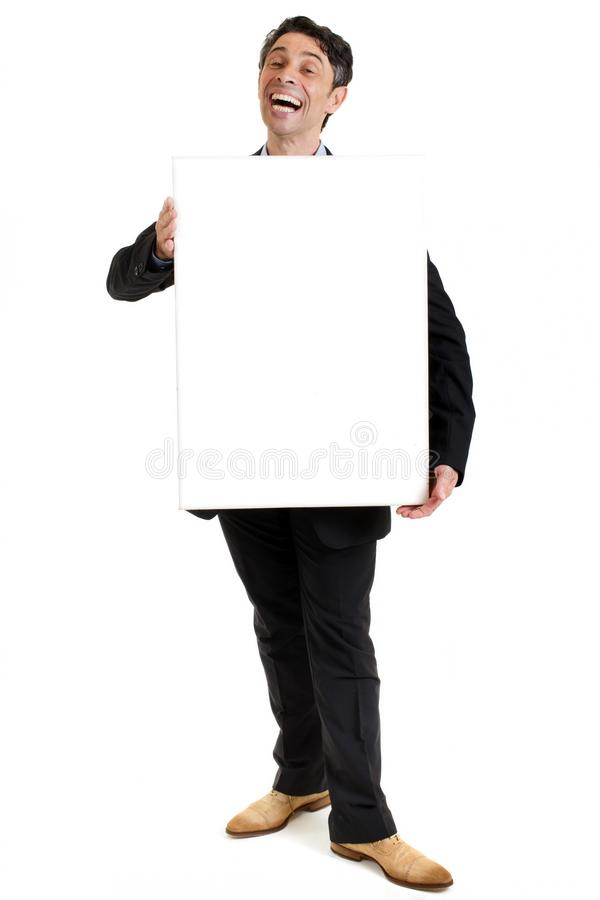 Hearty salesman with a cheesy smile. Hearty salesman with a cheesy wide toothy smile standing holding a blank rectangular sign board in front of his chest as he royalty free stock image