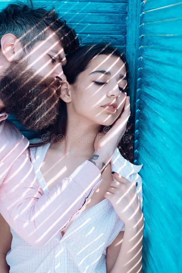 Heat concept. Couple chilling near jalousie, stripes of sunlight and shadow on faces. Girl in unbuttoned shirt and man royalty free stock image