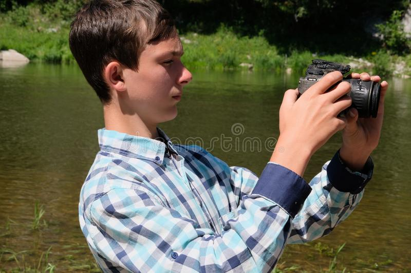 Heat or the effects of fire. The camera melted in the hands of a teenager. A strange situation on the river bank. A guy in a plaid stock photo