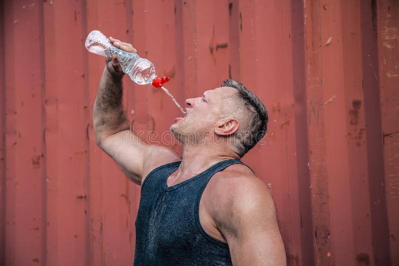Heat exhaustion bodybuilder, is raising a bottle of water. He is pouring out aqua to his mouth to cool himself off.  stock image