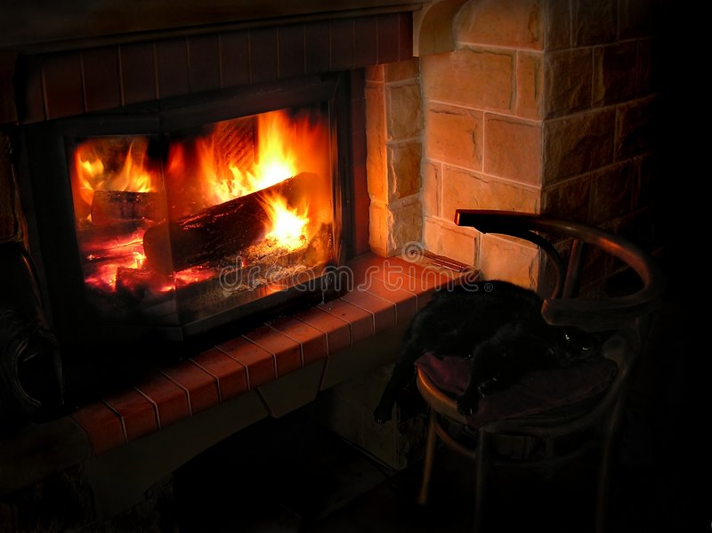 Heat at hole. A worm evening, cat seating in front of fire stock photos