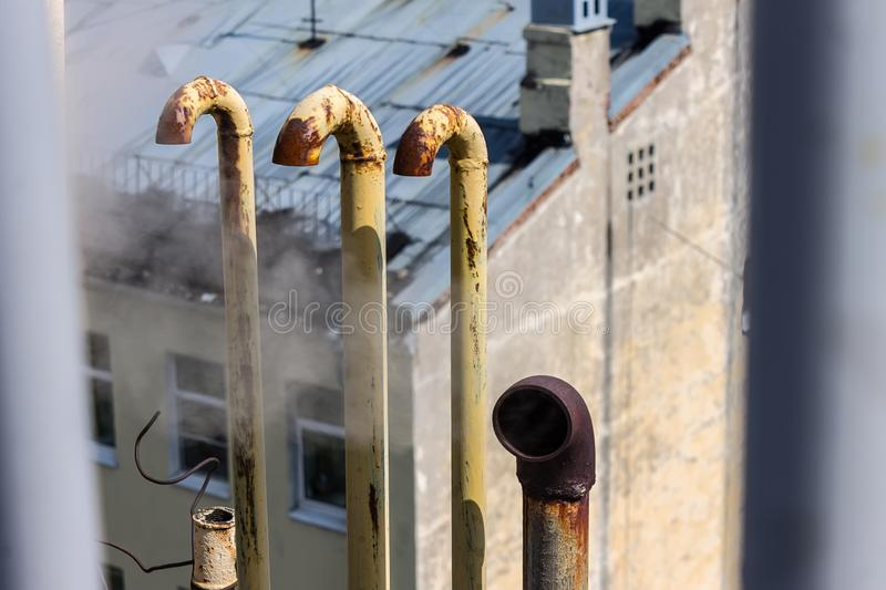 Heat pipes from which hot steam comes out on the roof of the building royalty free stock photo