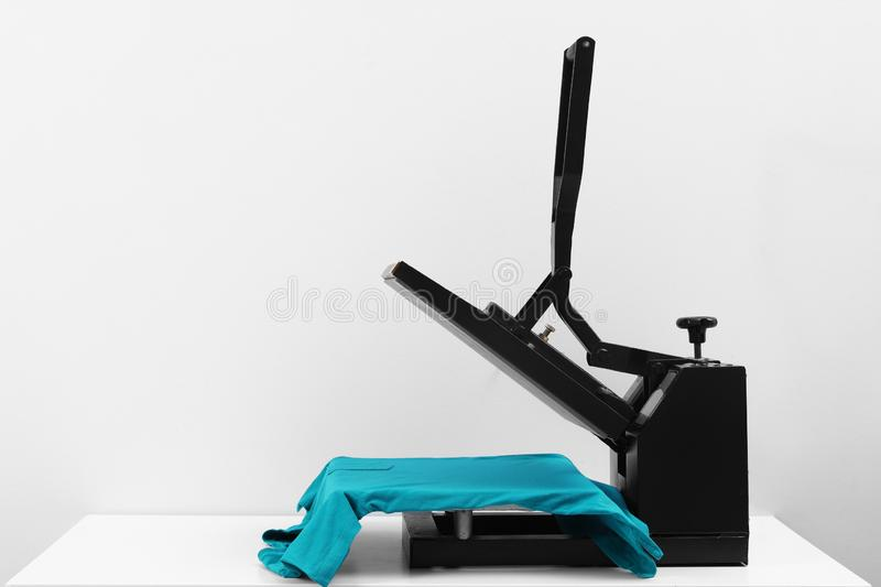 Heat press machine with t-shirt on table against light background. Space for text royalty free stock image