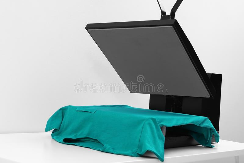Heat press machine with t-shirt on table  light background. Heat press machine with t-shirt on table against light background royalty free stock photos