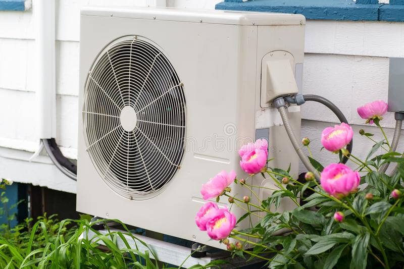 Heat Pump. Air conditioning/ Heat pump unit on the side of a home among the flowers stock photo