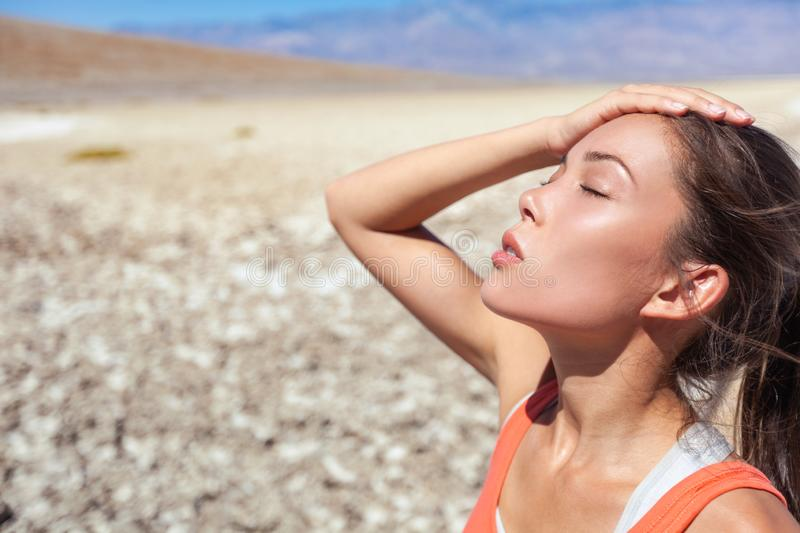 Heat stroke tired dehydrated girl under the desert sun hot temperature summer weather danger. Asian woman sweating exhausted royalty free stock photo