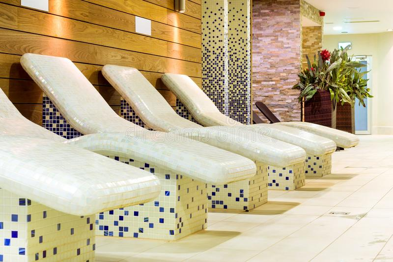 Heated relaxation chairs with tiles. SPA holidays. Heated relaxation chairs, covered with ceramic tiles. SPA holidays in stylish interiors, decorated with stock photo