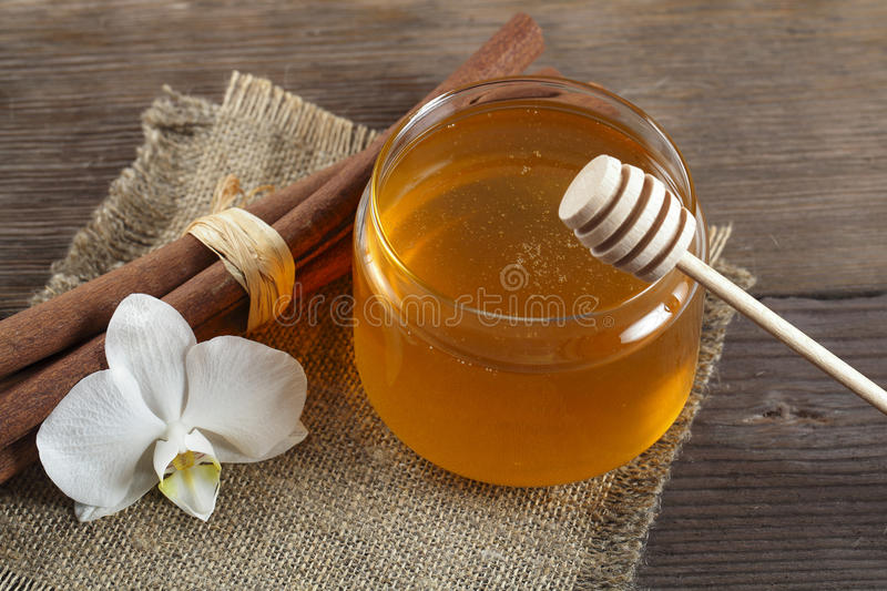 Heather honey and cinnamon on wooden table. Golden honey with honeystick, white orchid flower and cinnamon on wooden table royalty free stock photo