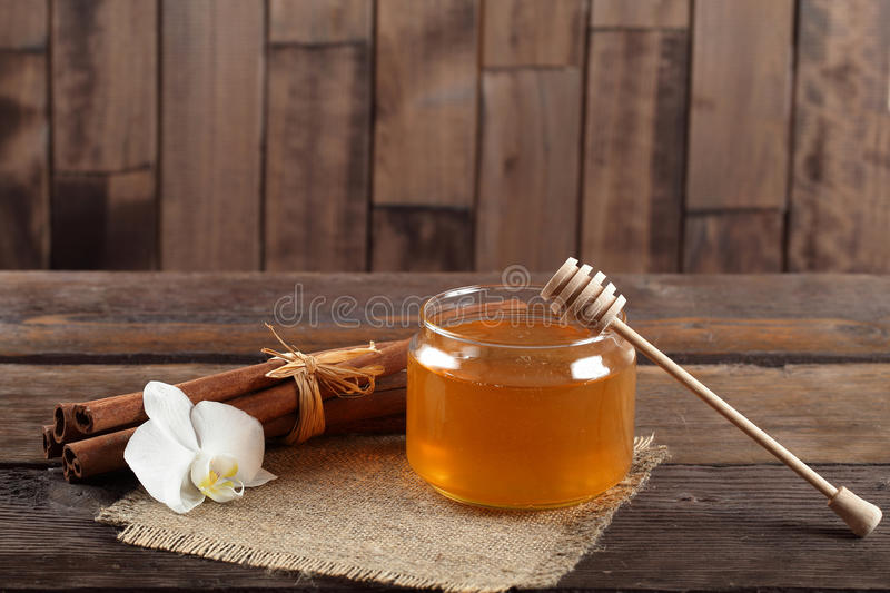 Heather honey and cinnamon on wooden table. Golden honey with honeystick, white orchid flower and cinnamon on wooden table stock photo