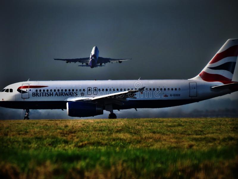 Heathrow congestion. Aircraft lining up for takeoff at Heathrow Airport as another takes stock image