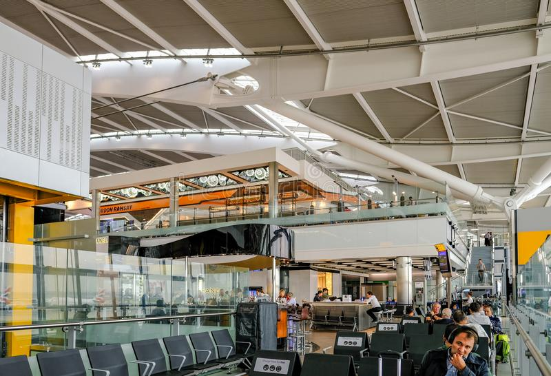 Heathrow, Terminal 5, London, UK - September 25, 2017: Quiet sea. Ting area with people in terminal 5. Shot shows people sitting waiting for flights stock image