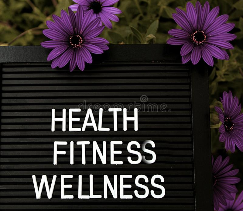 Health, Fitnes, Wellness - Heathy concept - Isolated text on black background with colorful flowers. Heathy concept - Isolated text on black background with royalty free stock photos