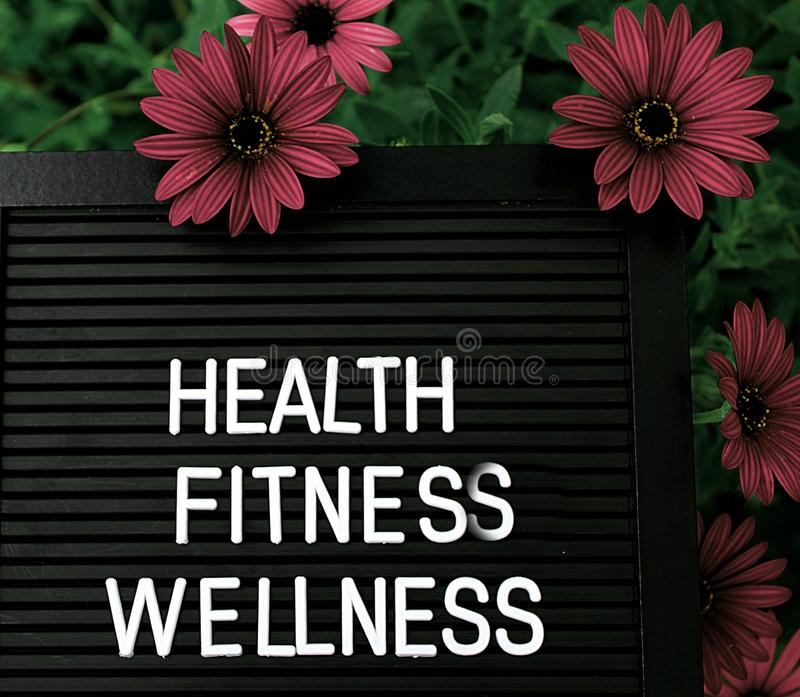 Health, Fitnes, Wellness - Heathy concept - Isolated text on black background with colorful flowers. Heathy concept - Isolated text on black background with royalty free stock photography