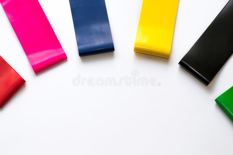 Heathy livsstilbegrepp - elastiska konditiongummiexpanders för kvinnor som isoleras på vit bakgrund Färgrika sportmusikband Cardi royaltyfri fotografi