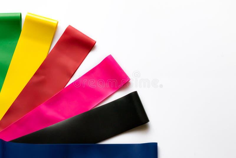 Heathy livsstilbegrepp - elastiska konditiongummiexpanders för kvinnor som isoleras på vit bakgrund Färgrika sportmusikband Cardi arkivbild