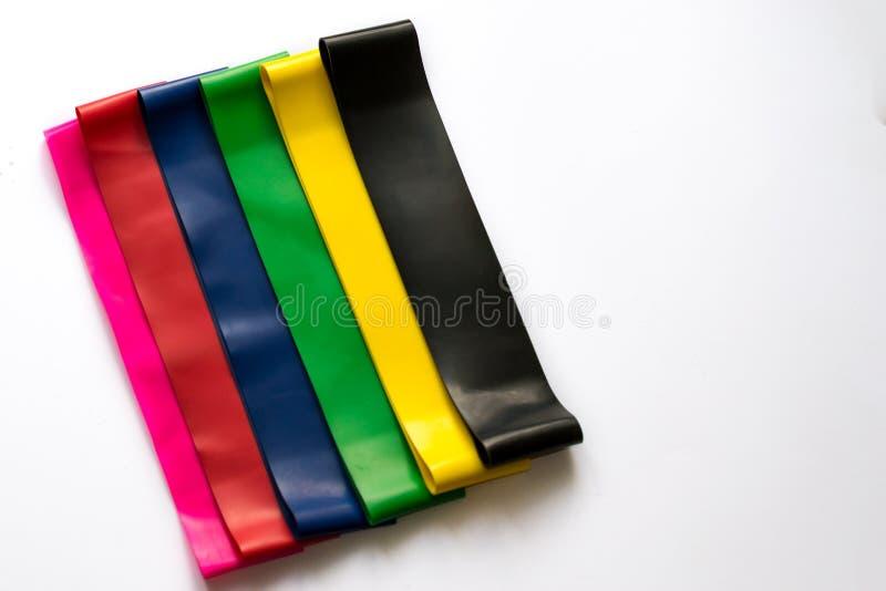 Heathy livsstilbegrepp - elastiska konditiongummiexpanders för kvinnor som isoleras på vit bakgrund Färgrika sportmusikband Cardi royaltyfri foto