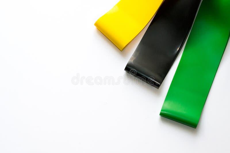 Heathy livsstilbegrepp - elastiska konditiongummiexpanders för kvinnor som isoleras på vit bakgrund Färgrika sportmusikband Cardi royaltyfria bilder