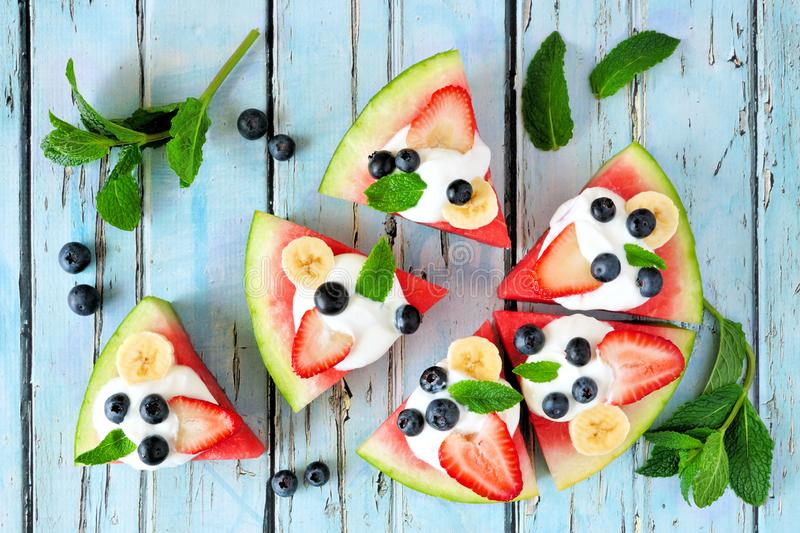 Heathy watermelon pizza witHealthy watermelon pizza with blueberries, strawberries, bananas and yogurt, top view over blue wood. Heathy watermelon pizza with stock photos