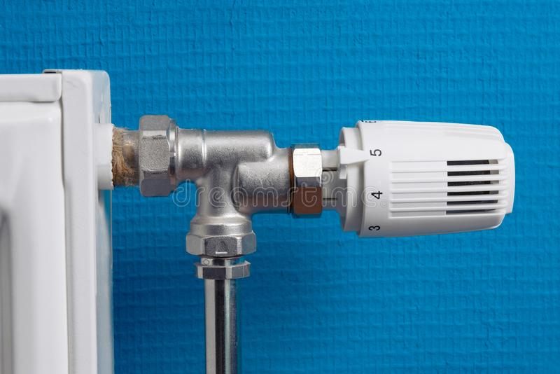 Heating. Radiator with regulator in front of blue wall stock photo