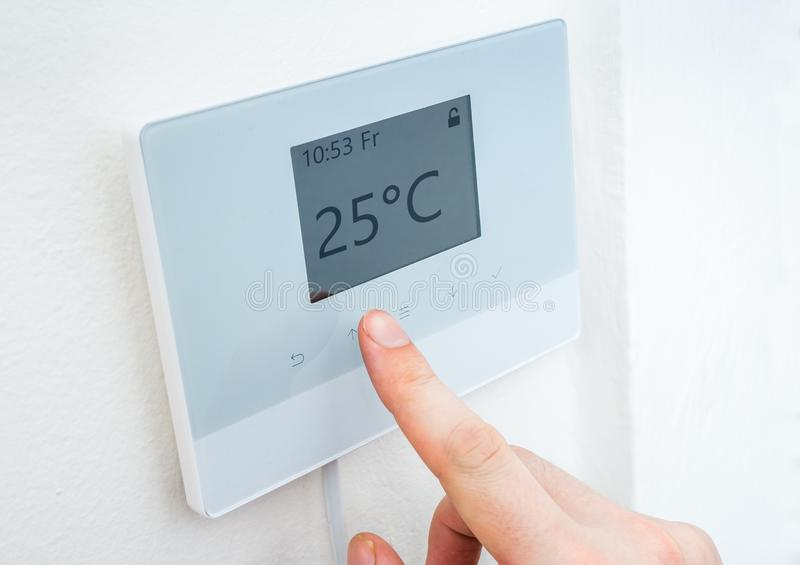 Heating concept. Hand is adjusting temperature in room on digital thermostat control. stock photo