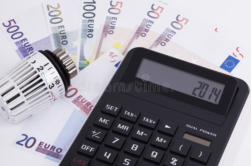 Heating costs 2014. Image shows heating thermostat, banknotes and calculator stock photo
