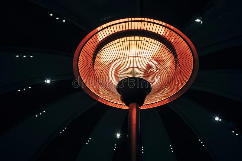 The heating element of the blow heater was heated to red in a dark room. Spiral heated to red. Infrared heater in the grid. room royalty free stock photography