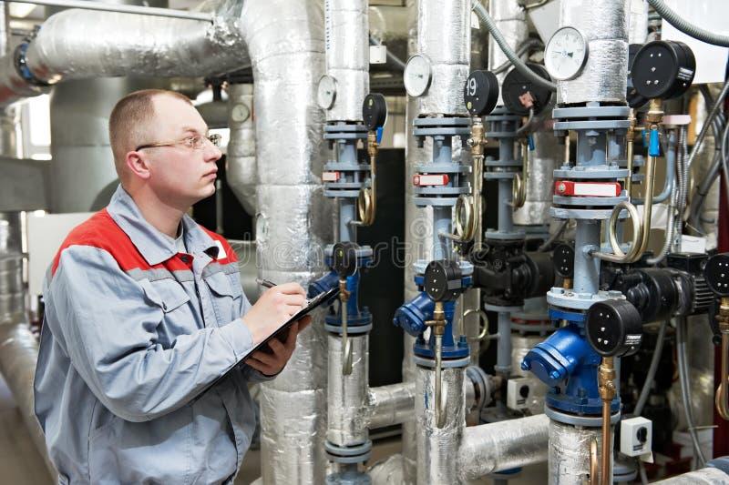 Heating engineer in boiler room royalty free stock photo