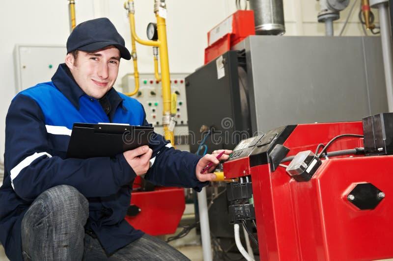 Heating engineer repairman. Maintenance repairman engineer of heating system equipment in a boiler house stock photos