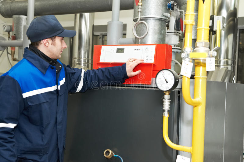 Heating engineer repairman. Maintenance engineer checking technical data of heating system equipment in a boiler house stock photo
