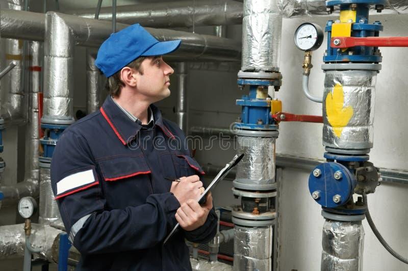 Heating engineer repairman. Maintenance repairman engineer of heating system equipment in a boiler house stock photography