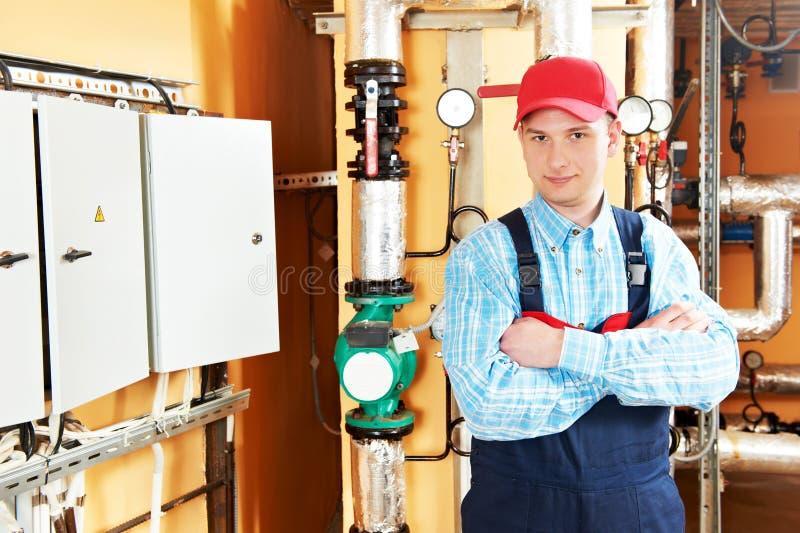 Heating engineer repairman in boiler room. Maintenance repairman engineer of heating system equipment in a boiler house royalty free stock photos