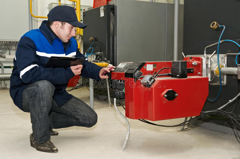 Heating engineer works with boiler. Maintenance engineer tuning heating system equipment in a boiler room stock photos