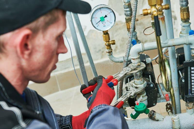 Heating engineer or plumber in boiler room installing or adjusting pipeline. Heating equipment inspecting. engineer or plumber in boiler room screwing or royalty free stock photo