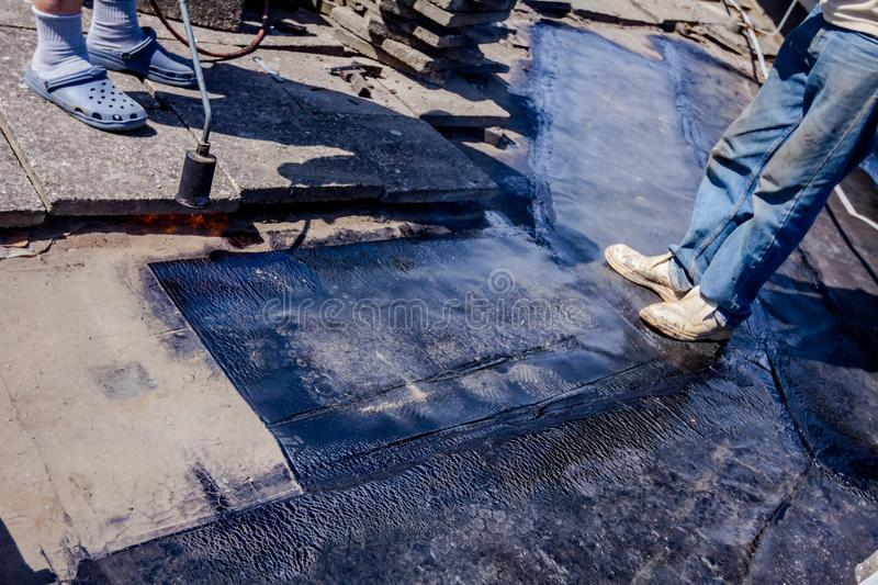 Teamwork at roofing installation resin. Heating and melting of bitumen surface by flame from gas torch. Worker adjusts bituminous cover for roofing felt, smears royalty free stock image