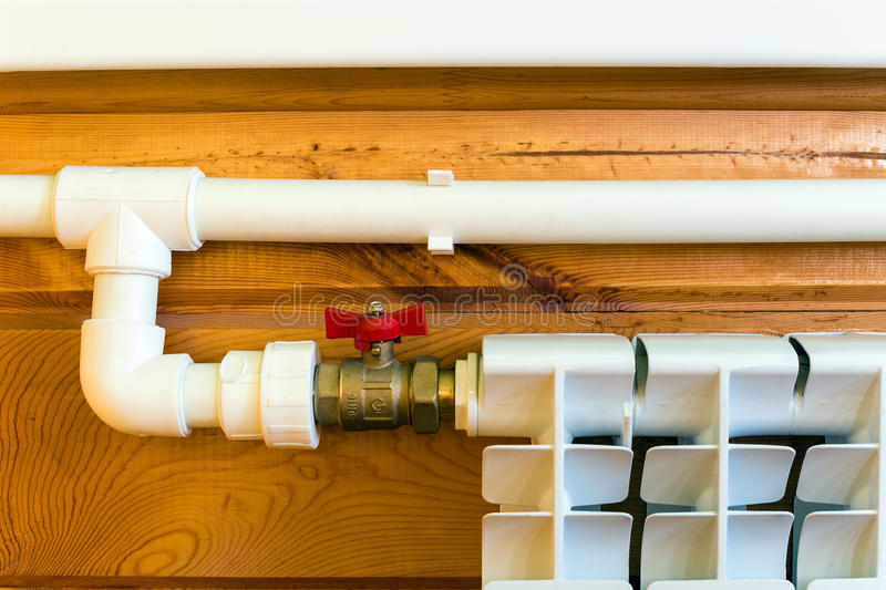 Heating radiator. And polypropylene pipes in a wooden house royalty free stock images